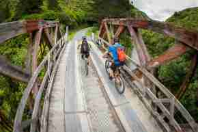 Remutaka Cycle Trail_two people mountain biking restored bridge