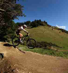 Mini enduro Rivenrock MTB Park_White tee mountain biker wheelie taking jump dirt track